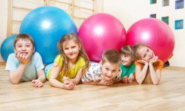 13138851 - five happy kids lie in gym with large balls
